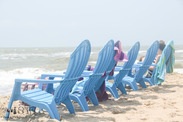 row of blue chairs at the beach