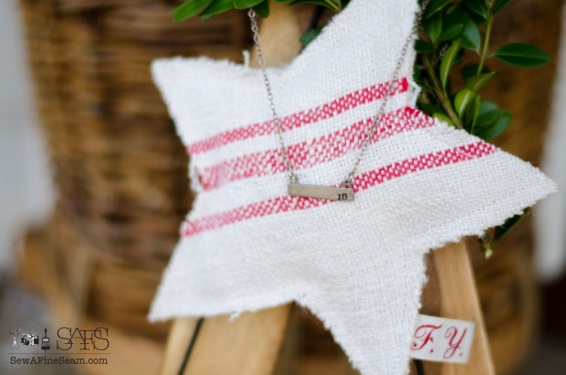 handmade grain sack ornament and necklace used to decorate a wooden ski ornament