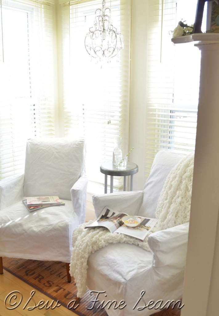 white slipcovers on old leather chairs
