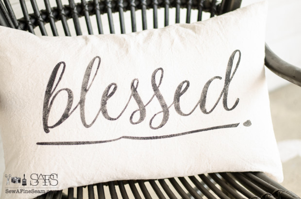canvas pillow with the word blessed stenciled in black