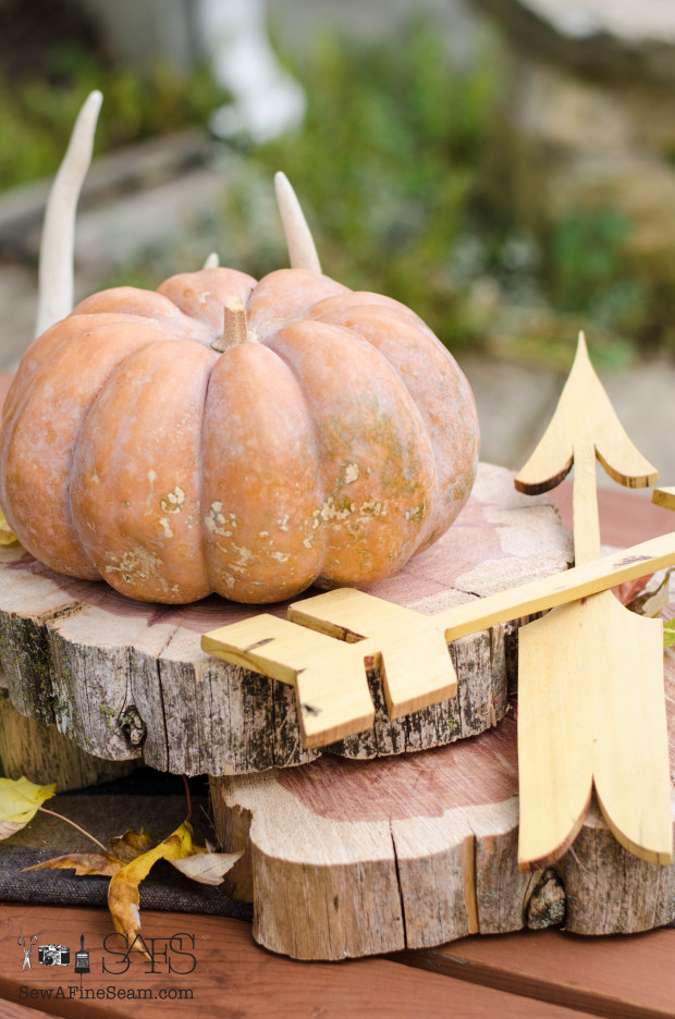 Fall centerpiece with pumpkins wood slices and wooden arrows