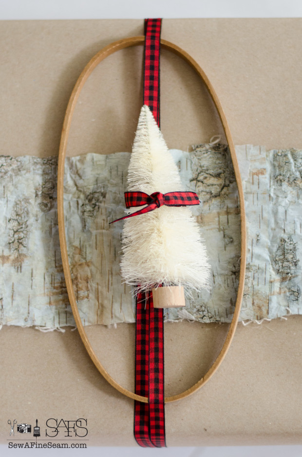 using birch bark ribbon vintage embroidery hoop, bottle brush tree, and checked ribbon to wrap a gift